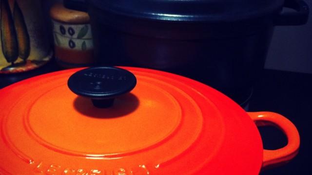 una cocotte nera e una arancione entrambe in ghisa